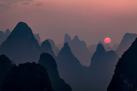 sun rising over Chinese mountains